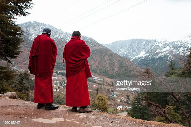 Monks at cliff observing below villlage