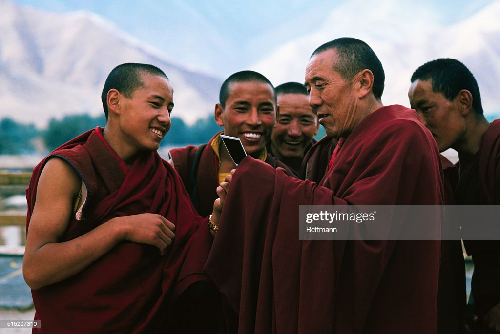 Monks at Jokhang Temple examining an instant Polaroid picture. To these holy people most cut off from the Western world, it is an amazing thing.