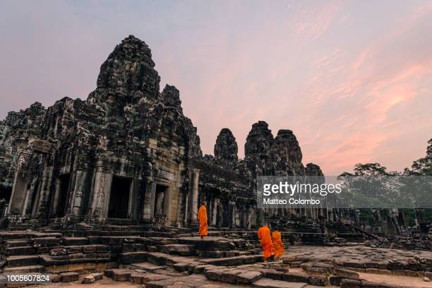 monks at sunrise inside angkor wat temple, cambodia - angkor stock photos and pictures