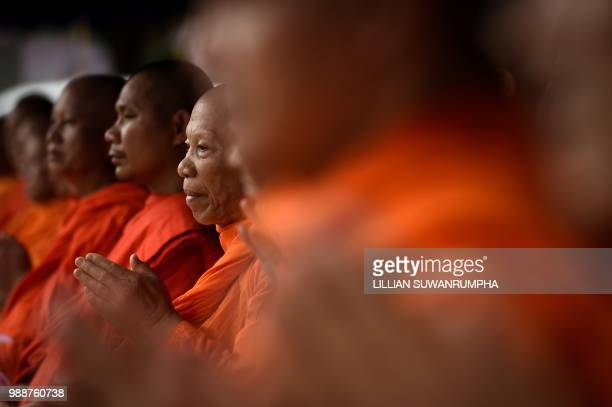 Monks attend a Buddhist prayer for the missing children near Tham Luang cave at the Khun Nam Nang Non Forest Park in the Mae Sai district of Chiang...