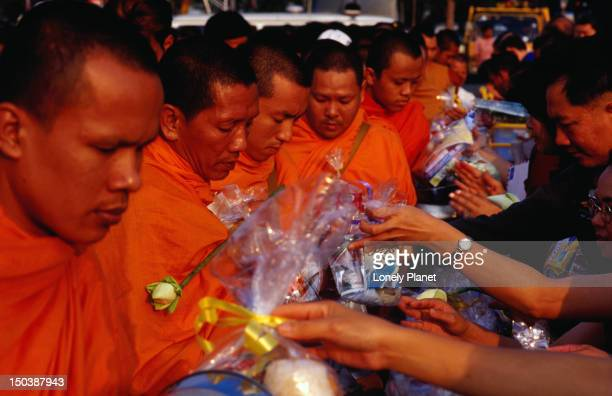 Monks collecting alms at merit-making ceremony in gardens of Sanam Luang as part of Thai New Year celebrations of Songkran Festival.
