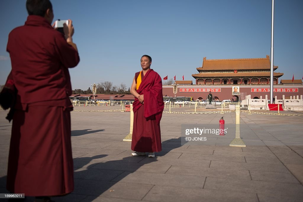 Monks from a Buddhist university take photos on Tiananmen Square in Beijing on January 24, 2013. Since China's reform period of the 1970's Buddhist temples ceased to receive state funding, with the government announcing a crackdown on religious profiteering as of October 2012. AFP PHOTO / Ed Jones
