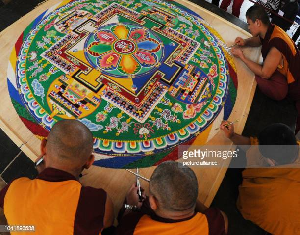 Monks from the exile monastery 'Sera Jhe' in South India finish a sand mandala at the ethnological museum in Hamburg, Germany, 20 January 2013. The...