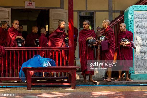 monks gather up at lunch hall entrance - merten snijders stock-fotos und bilder