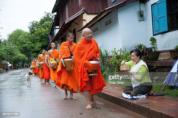 Monks getting donated food on the street of Luang Prabang Laos