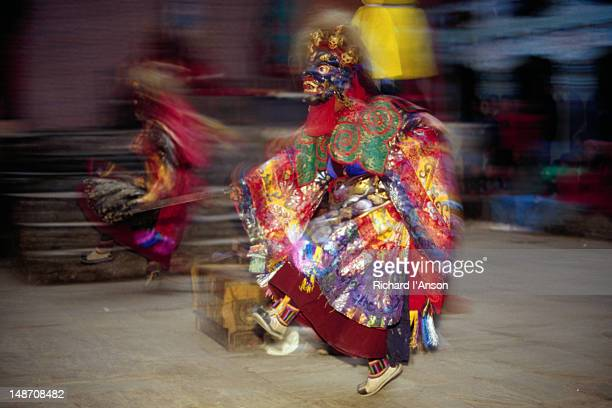 monks in elaborate mask and costume performing ritualistic dance at the mani rimdu festival at chiwang gompa (monastery). - mani rimdu festival stock pictures, royalty-free photos & images