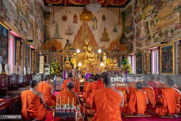 monks in front of buddha image. - tim bewer photos et images de collection