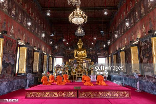 monks in front of buddha image. - tim bewer stock pictures, royalty-free photos & images