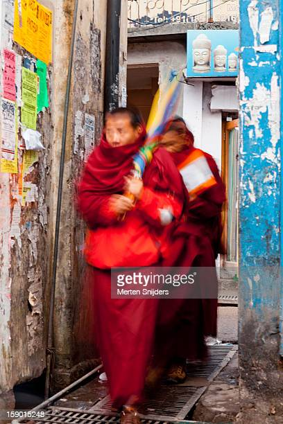 monks in motion through alley - merten snijders stockfoto's en -beelden
