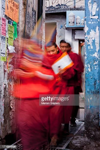 monks in motion through alley - merten snijders imagens e fotografias de stock
