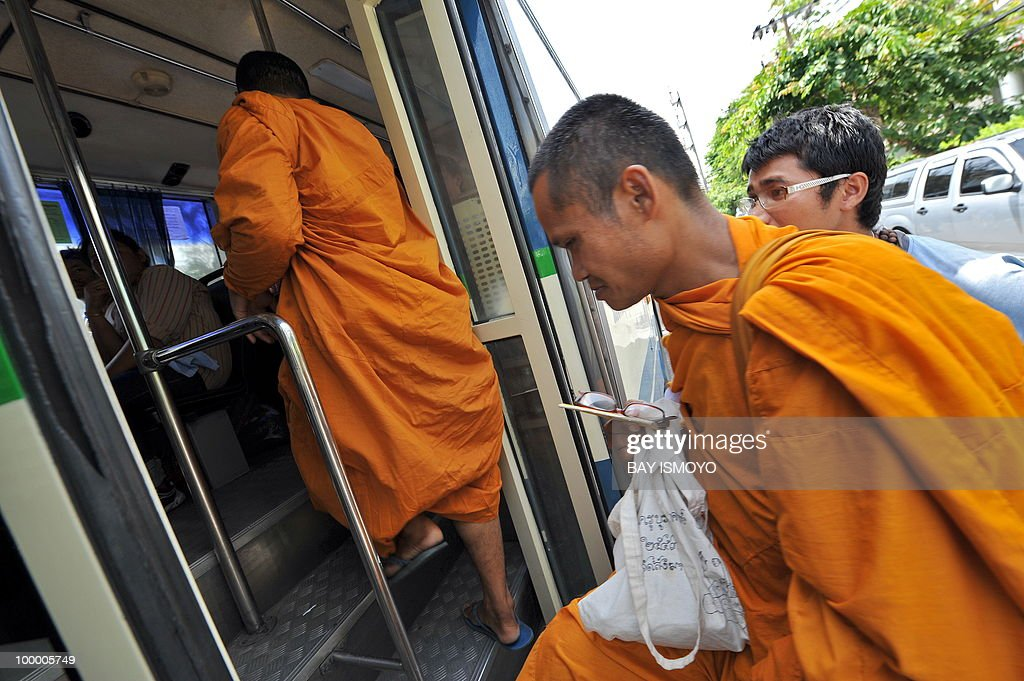 Monks join 'Red Shirt' anti-government protestors boarding buses out of their dismantled protest site a day after an army assault, in downtown Bangkok on May 20, 2010. Plumes of smoke hung over the Thai capital and gunfire crackled As troops moved to crush militants who went on the rampage after a deadly crackdown on their anti-government protest camp.