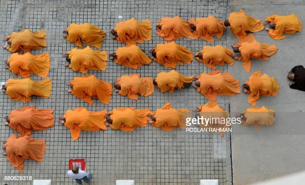 Monks leading devotees pray outside the Kong Meng San Phor Kark See Monastery during a ritual on the eve of Vesak day in Singapore on May 9 2017...