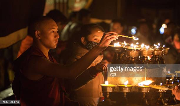 Monks light the lamps in Ramoche Temple on the Butter Lamp Festival on December 5 2015 in Lhasa Tibet Autonomous Region of China Votaries came to...