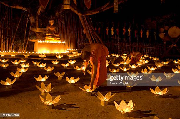 monks lighting candles at loi krathong festival - loi krathong stock photos and pictures