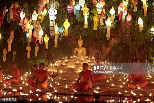 Monks of Pantao temple sit near candles as they mediate before releasing the lanterns to the sky during the opening ceremony of Yi peng festival at...