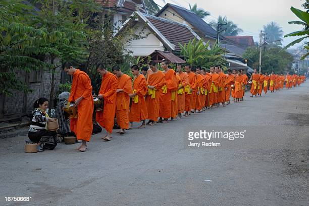Monks parade through the streets to receive alms in the morning in front of ancient Wat Xiengthong built in 1560 by King Setthathirath It is today a...