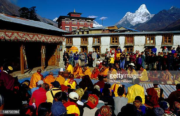 monks performing ceremony at mani rimdu festival with tengboche monastery and ama dablam in background. - mani rimdu festival stock pictures, royalty-free photos & images
