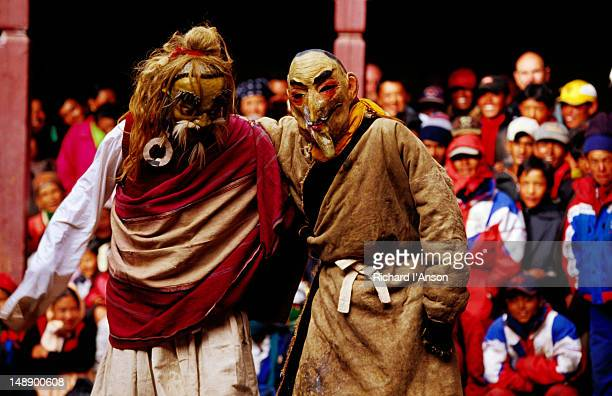 monks performing masked play with spectator at mani rimdu festival. - mani rimdu festival stock pictures, royalty-free photos & images
