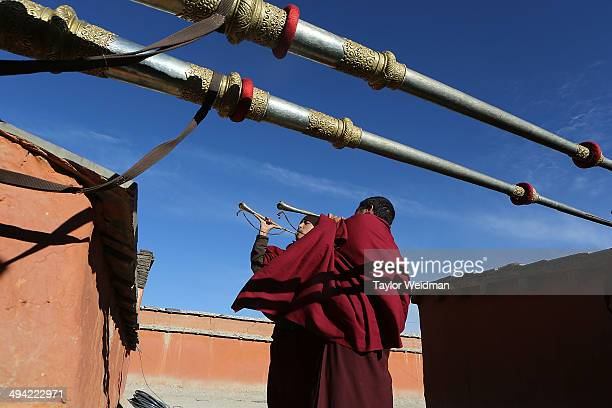 Monks play gyaling and dungchen, Tibetan ritual instruments, from a monastery rooftop at the end of a ceremony during the Tenchi Festival on May 24,...