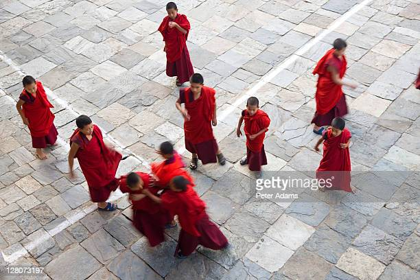 monks playing tag in courtyard of dzong monastery, trongsa, bhutan - peter adams stock pictures, royalty-free photos & images