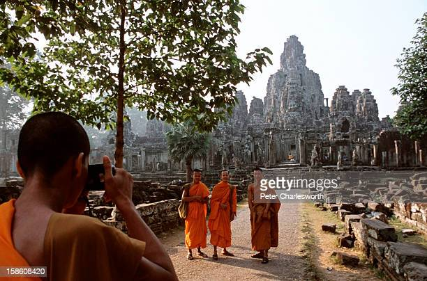 Monks pose for photographs against the backdrop of the Bayon Temple in the early morning