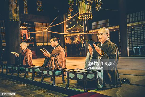 monks praying at buddhist chion-ji temple in kyoto, japan - tempel stockfoto's en -beelden