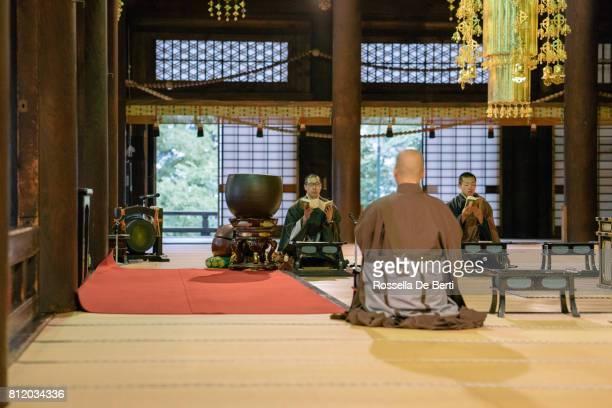 仏教寺院の中朝のセレモニー中に祈る僧侶