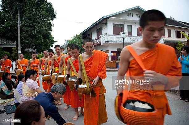 monks receive food offerings - laotian culture stock pictures, royalty-free photos & images