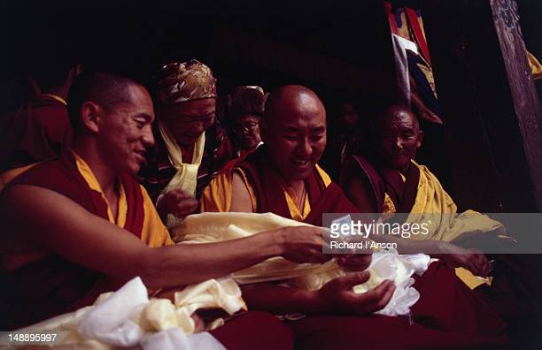 monks receiving offerings of money from visitors at the mani rimdu festival at chiwang gompa (monastery). - mani rimdu festival stock pictures, royalty-free photos & images