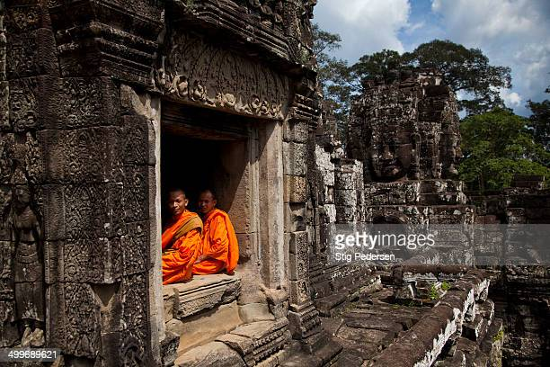 CONTENT] 2 monks resting at the Bayon temple inside Angkor Wat