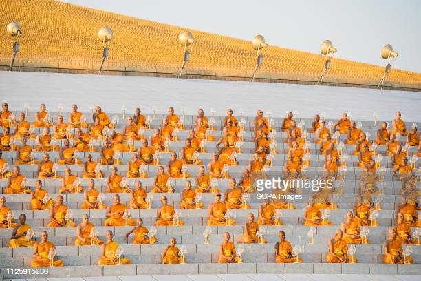 Monks seen praying while holding lanterns during the yearly Makha Bucha ceremony. Buddhist devotees celebrate the annual festival of Makha Bucha, one...