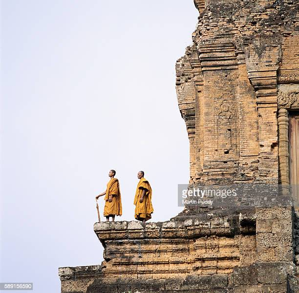 monks standing atop angkor wat - angkor wat stock pictures, royalty-free photos & images