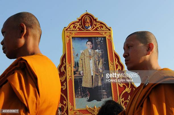 Monks walk past a large portrait of Thailand's King Bhumibol Adulyadej during a ceremony marking his 81st birthday anniversary at Sanam Luang square...