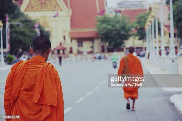 Monks Walking On Road Leading Towards Temple