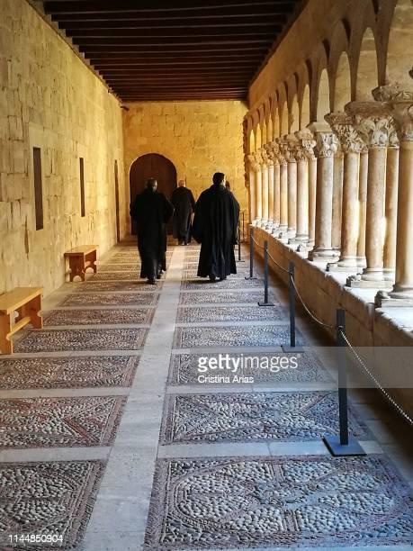 Monks walking through the cloister of the romanesque monastery of Santo Domingo de Silos, Burgos, Castile and Leon, Spain.