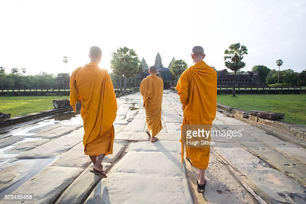 monks walking towards temple, angkor wat, cambodia - hugh sitton imagens e fotografias de stock