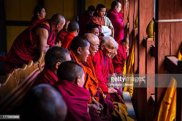 monks watching the paro tsechu (festival) - paro district stock pictures, royalty-free photos & images
