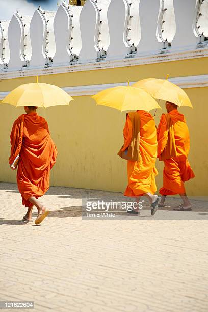 monks with yellow umbrellas outside the grand palace, phnom penh, cambodia - phnom penh stock pictures, royalty-free photos & images