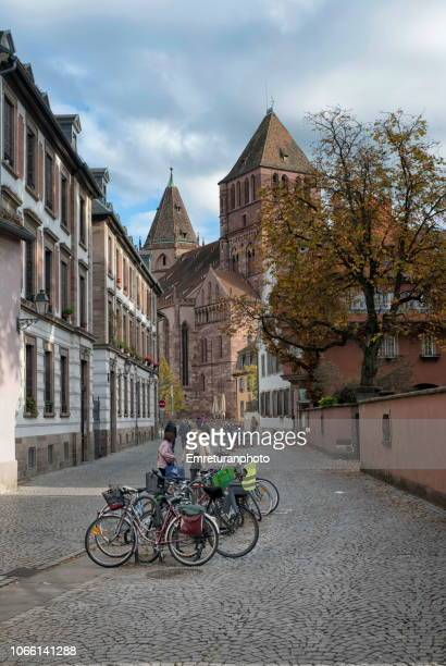 monnaie street with parked bikes and pedestrians and st.thomas church tower at the background - emreturanphoto stock pictures, royalty-free photos & images