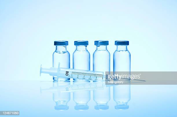 monochromatic image of four glass vials and a syringe - vaccination stock pictures, royalty-free photos & images
