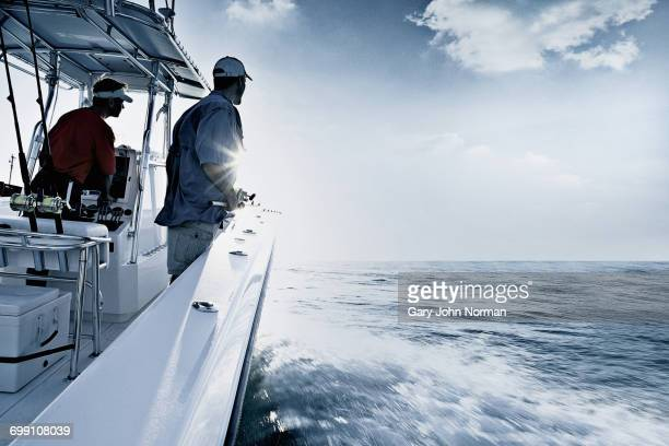 'Monochromatic shot of two men driving and fishing from speedboat, Miami, USA'