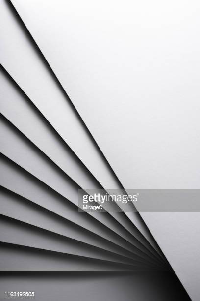 monochrome white stacking paper fanned out - miragec stock pictures, royalty-free photos & images