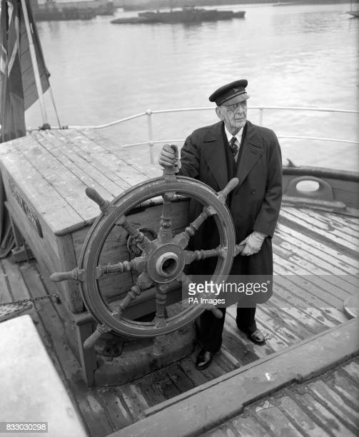 Monocled Captain C E Irving CB one of the last two surviving apprentices to have trained aboard the Cutty Sark at the wheel as the ship lies at...