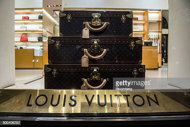 Monogrammed 'Alzer' luggage cases sit stacked on display in the window of a Louis Vuitton luxury store operated by LVMH Moet Hennessy Louis Vuitton...