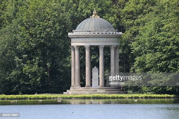 Monopterus in Parkanlage Schloss Nymphenburg Muenchen hinter Wasserflaeche vor Waldkulisse
