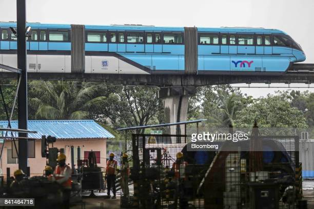 A monorail train operated by Mumbai Metropolitan Region Development Authority travels along an overhead track past the Mumbai Metro Rail Corp casting...