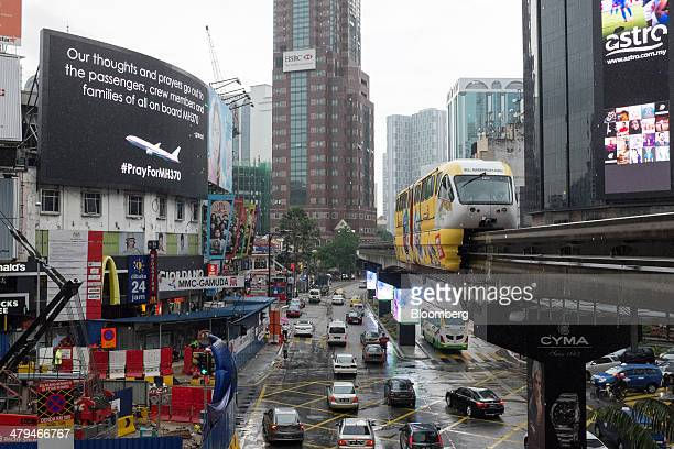 Monorail train, operated by Rapid Rail Sdn Bhd, moves along an elevated track past a billboard for missing Malaysian Airline System Bhd. Flight 370...