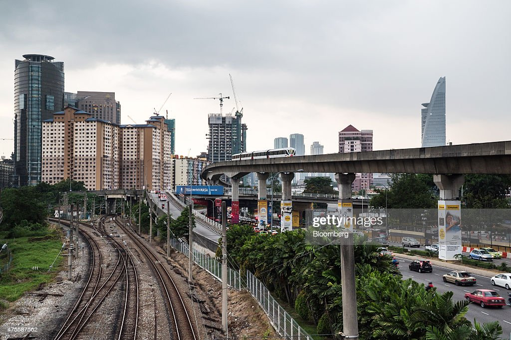 Monorail train operated by Rapid Rail Sdn Bhd. travels along an elevated track as vehicles drive along a highway next to rail tracks in Kuala Lumpur, Malaysia, on Wednesday, May 27, 2015. Malaysia's ringgit fell for a sixth day on June 1, in the longest stretch of losses since 2013 as falling oil prices weigh on the nation's finances. Photographer: Sanjit Das/Bloomberg via Getty Images