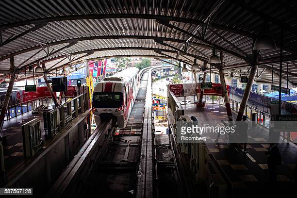 Monorail train operated by Rapid Rail Sdn Bhd travels along an elevated track as commuters stand on a platform at the Bukit Bintang station in Kuala...