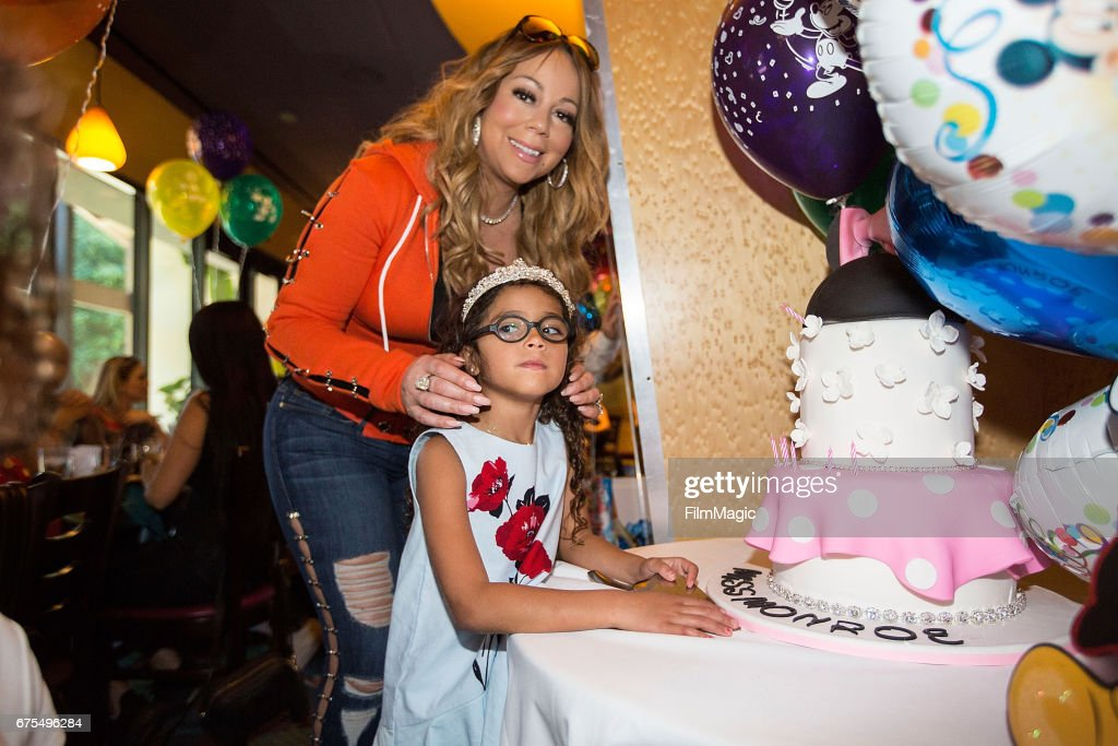 Monroe Cannon poses next to her birthday cake as mom Mariah Carey looks on at Disneyland on April 30, 2017 in Anaheim, California.